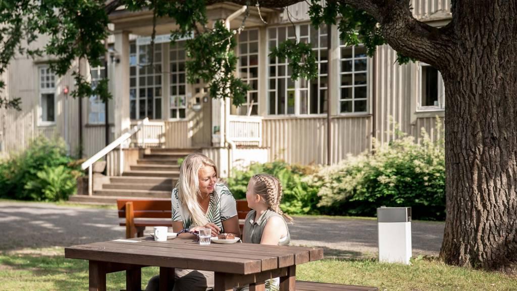 Nainen ja tyttö kahvilla Voipaalan puutarhassa