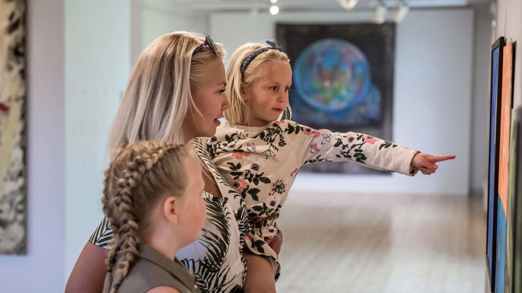 äiti ja tyttäret tutkivat Voipaalan taidekeskuksen näyttelyä