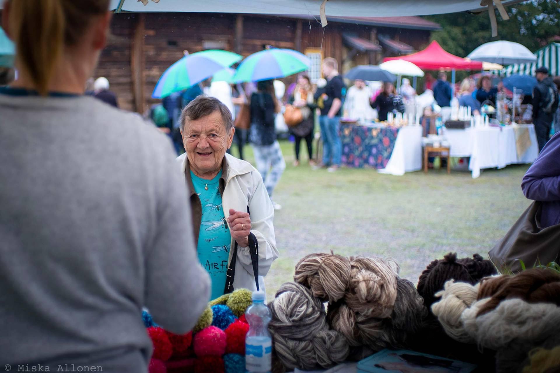 Vanhempi nainen ostaa lankoja Voipaalan markkinoilla