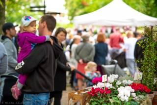 Lapsi miehen sylissä ja kukkia Voipaalan markkinoilla