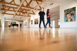 Kaksi lasta kävelee Voipaalan taidenäyttelytilassa