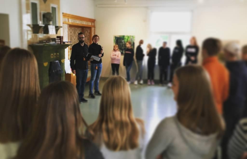 huone täynnä koululaisia, jotka näkyvät epätarkasti. Kuvan tarkennus ohjaajissa, mies ja nainen seisovat.